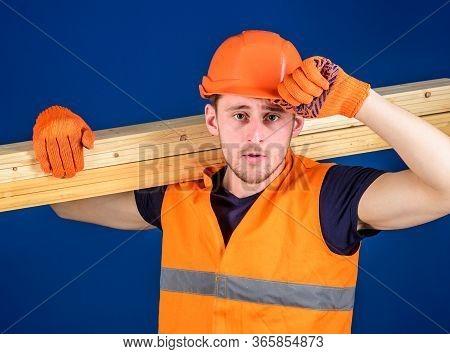 Man In Protective Gloves Holds Visor Of Helmet, Corrects Hard Hat On Head, Blue Background. Carpente