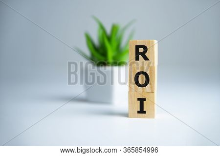 Return On Investment, Roi. Cube Wooden Block With Alphabet Building The Word Roi.