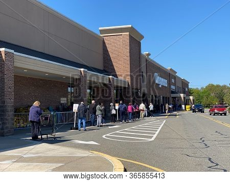 Woodbridge, New Jersey / Usa - May 7, 2020: Shoppers Wait Outside In A Line To Get Into The Wegmans