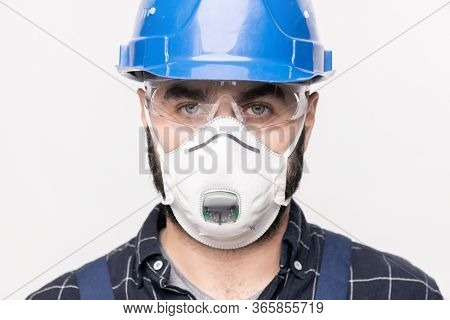 Head of contemporary engineer in hardhat and protective mask and eyeglasses standing in front of camera and looking at you