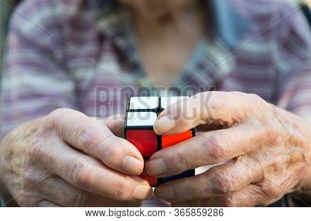 Closeup Of An Elderly Man Using A Rubix Type Cube Puzzle As Therapy For His Diminished Mental Capaci