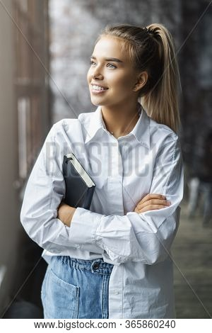 Student Girl In A White Shirt Smiles And Stands Near The Window. Portrait Of Incredibly Attractive W