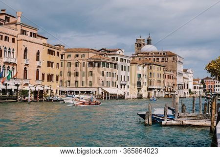 Tourists On The Waterfront In Venice, Against The Background Of The Ancient Facades Of Buildings Sta