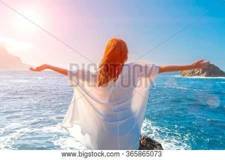 Happy Redheadwoman Wearing A White Shirt Breathing Fresh Air And Raising Arms On The Beach Of An Oce