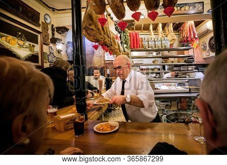 Granada, Spain: Elderly Barman Is Serving Ready-made Meals For Drinking Visitors Of Tapas Bar With V