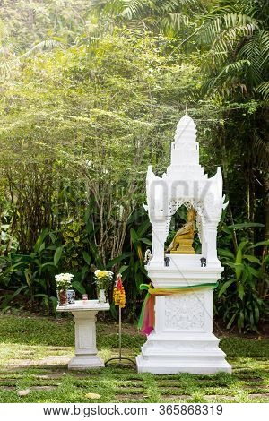White Spirit House In Green Garden In Thailand, Traditional Decorated House For Spirits