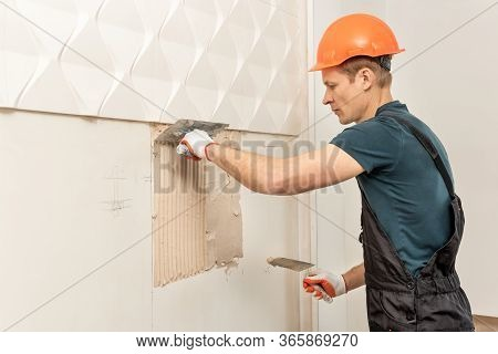 Installation Of Gypsum 3d Panel. The Worker Is Applying Adhesive To The Wall To Attach The Gypsum Ti