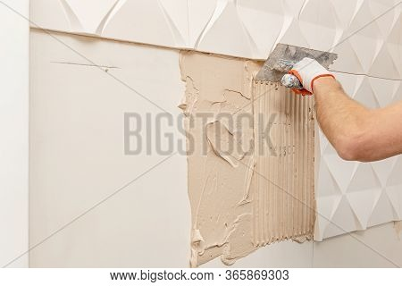 Installation Of Gypsum 3d Panel. A Worker Is Applying Adhesive To The Wall To Attach The Gypsum Tile
