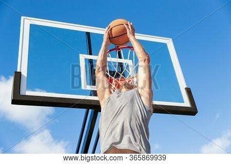 Basketball slam dunk man jumping to hoop throwing ball.