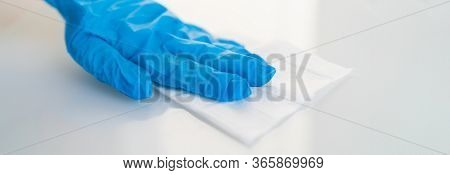 Surface cleaning against spreading of coronavirus person wearing gloves with antibacterial disinfecting wipe wiping glass table. banner panoramic background.