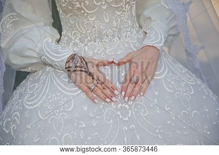 Bride Holding On To Belly Hands In Heart-shaped . The Bride Holds A Heart In Her Hand Over Her Belly