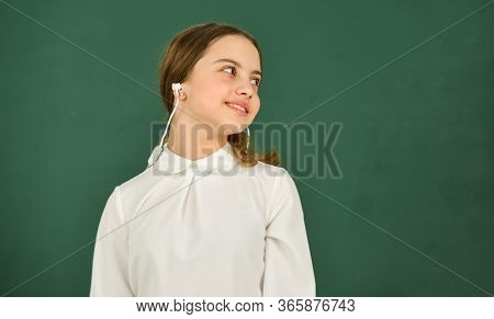 Listening Audio Book. Student Girl In Headphones At Chalkboard Background Copy Space. Audio Translat