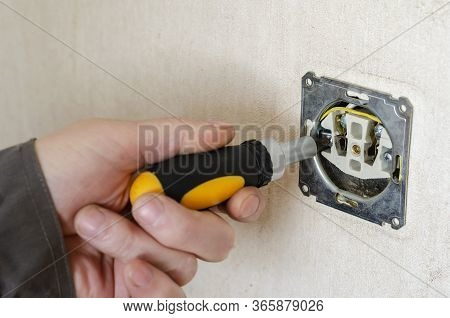 Male Hand With A Screwdriver Repairs An Electrical Outlet.
