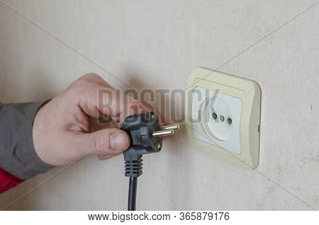 A Man S Hand In Work Clothes Pulls An Electric Plug From A Wall Outlet.