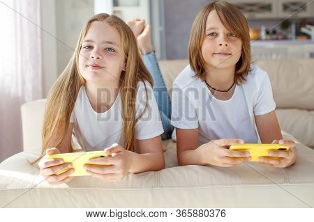 Children At Home Each Play Their Own Game. Brother And Sister Are Playing At Home. The Child Plays O