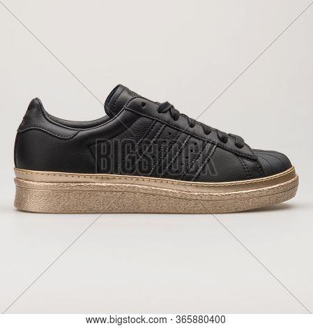 Vienna, Austria - August 13, 2018: Adidas Superstar Black And Gold Sneaker On White Background.