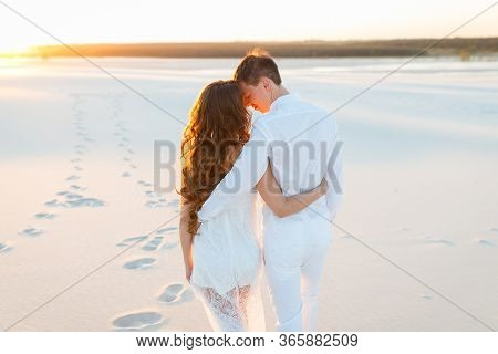 Young Couple Hugging In A White Desert During A Romantic Honeymoon Trip.