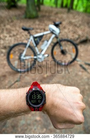 Biker Looking On Wearable Sports Watch And Mountain Bike On Forest Trail