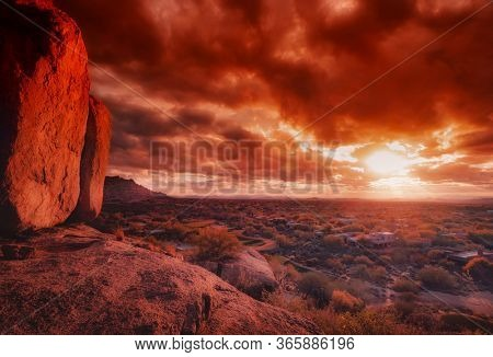 Giant boulders on mountain view overlook valley with wild stormy cloudscape at sunset.