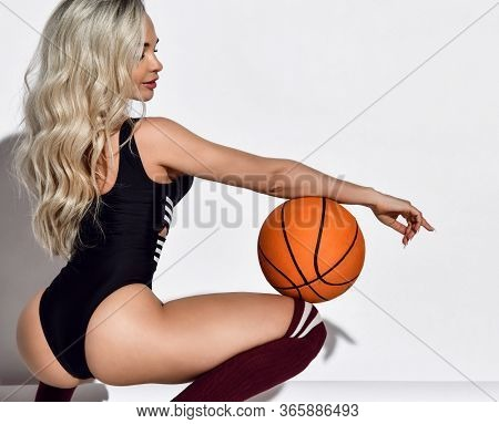 Beautiful Sexy Fitness Blonde Woman In Black Swimsuit, High Sport Socks And Sneakers Sitting With Ba