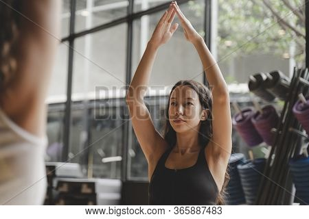 Pretty Young Woman Slim Body Doing Yoga In Padmasana Or Lotus Yoga Pose On Yoga Mat With Instructor