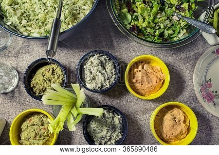 Healthy, Vegetarian Meal. Bowls With Various Dips And Salads, Celery Sticks