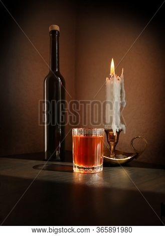 Still Life With Fruit Liqueur In The Vintage Small Glass, Black Bottle And Candlestick With Burning