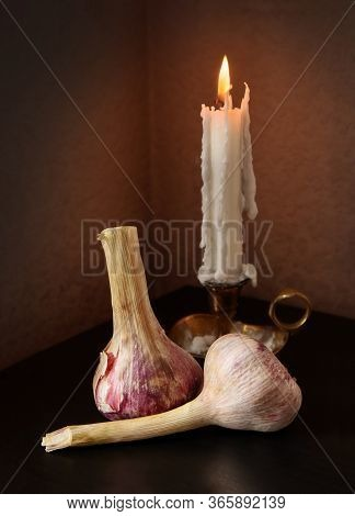 Two Garlic Bulbs And Candlestick With Burning Candle Against A Low Key Background. Retro Country Sty