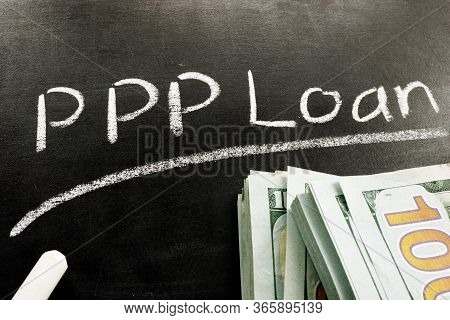 Ppp Loan Written On The Blackboard And Stack Of Cash From Paycheck Protection Program.
