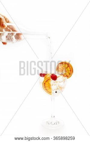 Barman Pouring Tonic Into A Cup Of Orange Gin Tonic Cocktail. White Background. Cold Drink Concept,