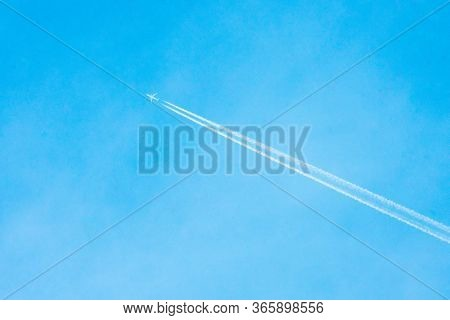 Airplane Flying In The Clear Blue Sky With White Trail Along The Route. Jet With Contrail In High Sp