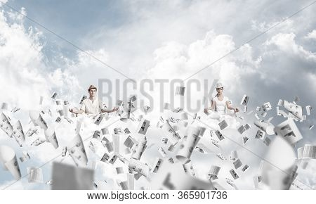 Young Couple Keeping Eyes Closed And Looking Concentrated While Meditating Among Flying Papers In Th
