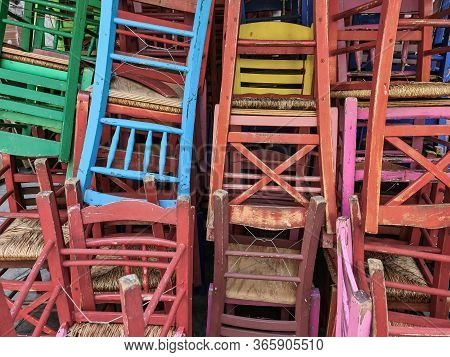 Colorful Wooden Chairs Stacked Outside. Day Sunny View Of Tavern Style Chairs In Random Disarray And