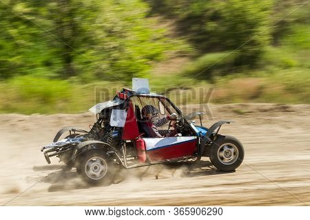 The Buggy Car Is Speeding Through Rough Terrain In Dusty Clubs. The Concept Of Extrieme Offroad Driv
