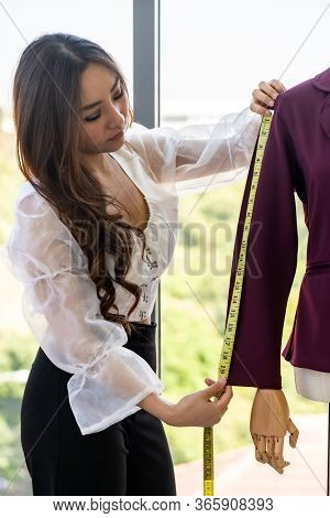 Close-up young adult asian fashion designer using measuring tape to measure suit arm at her atelier studio as sole owner. Using for entrepreneur small business startup concept.