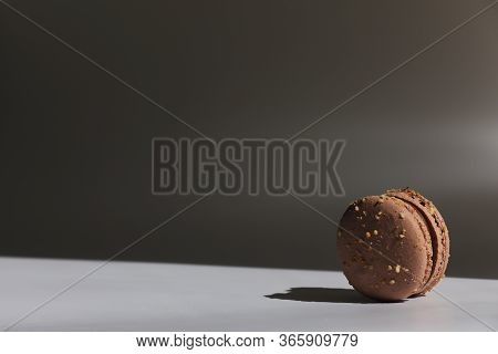 One Cake Of Brown Chocolate Macaron Or Macaroon With Shadow From Window. Delicious Macaroon Isolated