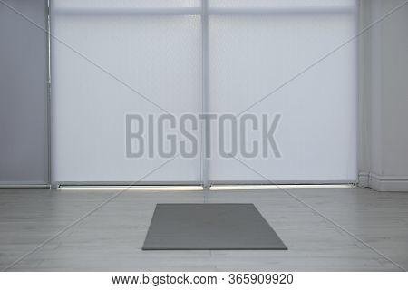 Unrolled Grey Yoga Mat On Floor In Room
