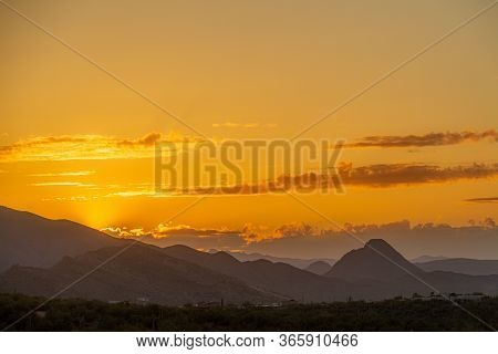 The Sun Setting Behind Mountains In The Sonoran Desert Of Arizona.