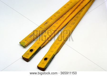 Yellow Wooden Folding Meterstick With Brass Ends Isolated On A White Background. Fully Extended It M
