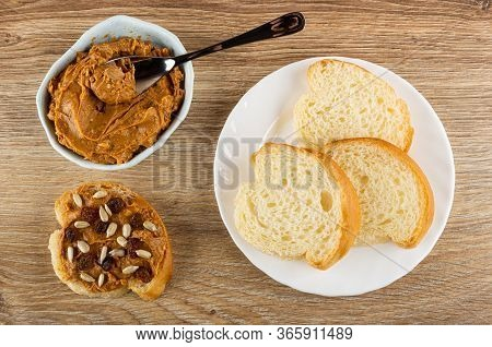 Spoon In Blue Glass Bowl With Peanut Butter, Sandwich With Peanut Pasta, Slices Of Bread In White Pl