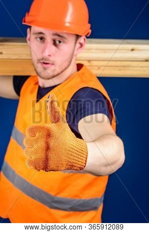Carpenter, Woodworker, Builder On Strict Face Carries Wooden Beam On Shoulder. Wooden Materials Conc