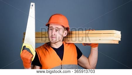Woodcraft Concept. Man, Handyman In Helmet, Hard Hat Holds Handsaw, Looks At Sharp Blade, Grey Backg