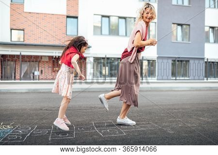 Outdoor Image Of Happy Little Girl Playing Hopscotch With Her Mother On Playground Outdoors. Child P