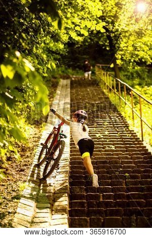9 Years Girl Bring Up For The Stairs Her Bicycle In The Sunny Day