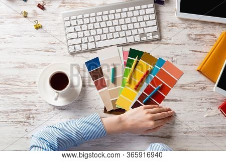 Web Designer Choosing Colors From Swatches At Wooden Desk. Office Workplace With Computer Keyboard A