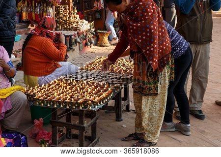 Kathmandu, Nepal - November 13, 2016: Woman At Boudhanath Stupa Lighting Up Butter Candles.