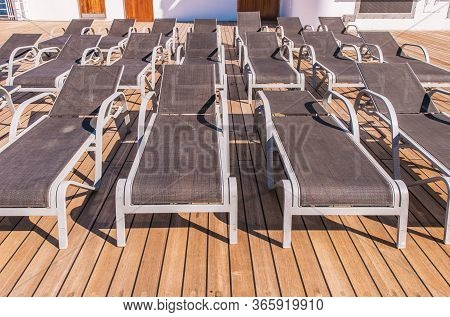 Close Up Of Rows Of Outdoor Unfolded Gray Lounge Chairs On Wooden Deck Of Vacation Resort.