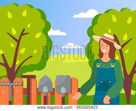 Happy Smiling Woman Wearing Garden Uniform And Hat Standing Near Fence With Gardening Tools On It. A