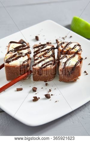 Chocolate pancake in ceramic white plate. Roll with mascarpone cheese, cream cheese, kiwi, coconut, chocolate topping and condensed milk close up. Gourmet appetizer, restaurant food, sweet meal