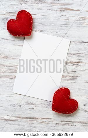 Blank Sheet Of Paper And Red Love Hearts On Wooden Table. View From Above On Romantic Composition Wi